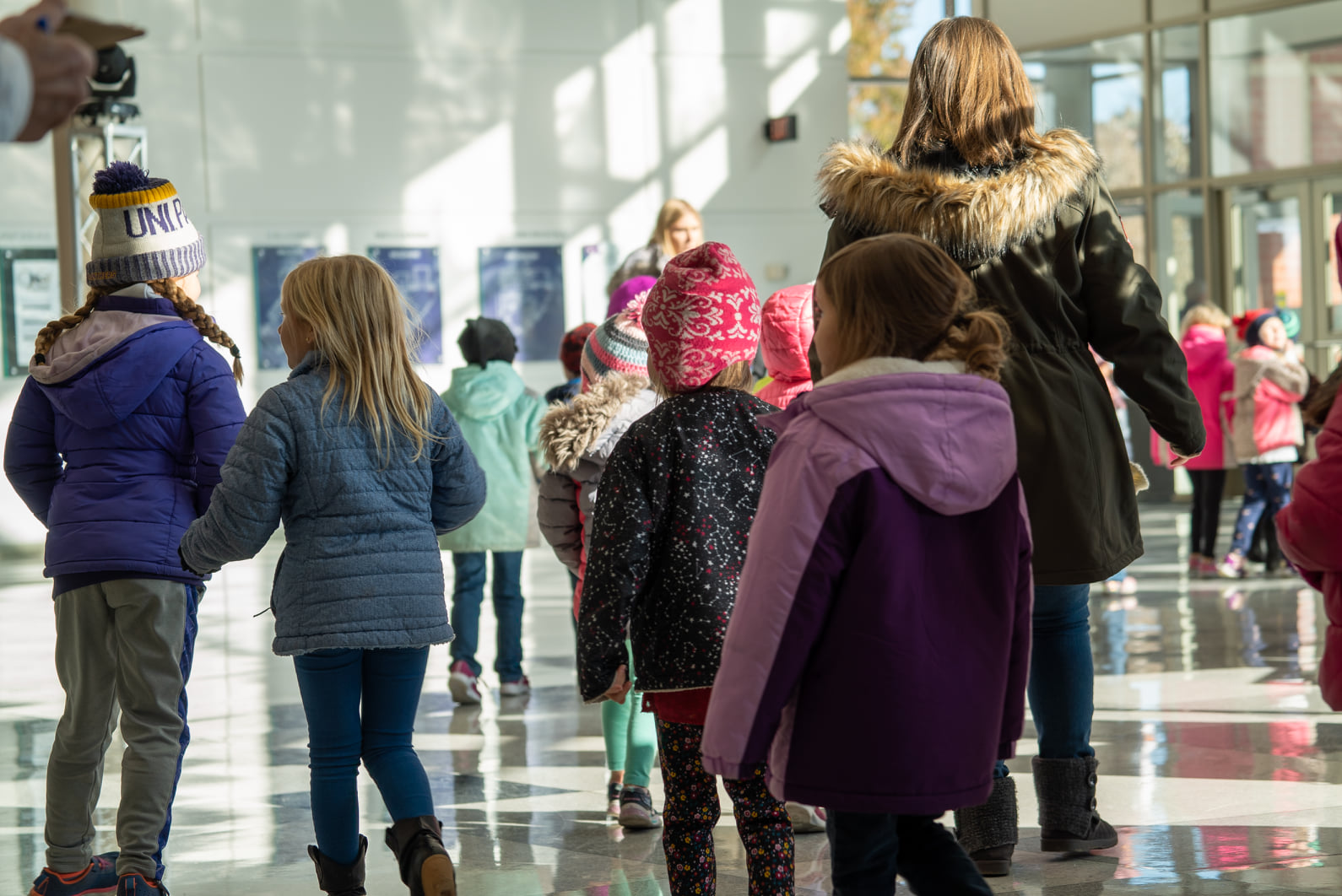 Children filing through the lobby of the Gallagher Bluedorn in winter clothes.