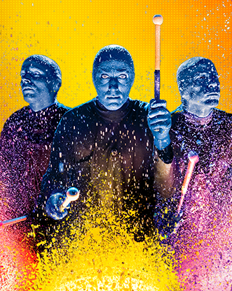 Blue Man Group playing a drum with paint splatters