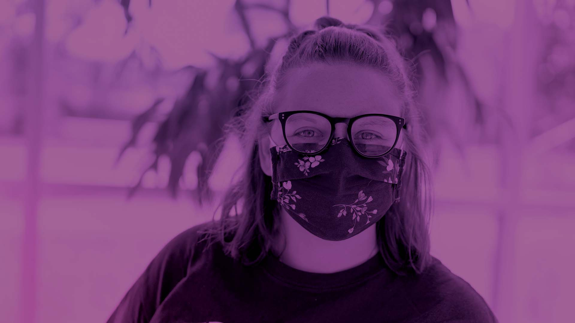 A person smiling with a mask on. There is a purple gradient overlay on them