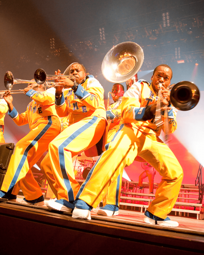 People in yellow drumline suits stand with various brass instruments on stage