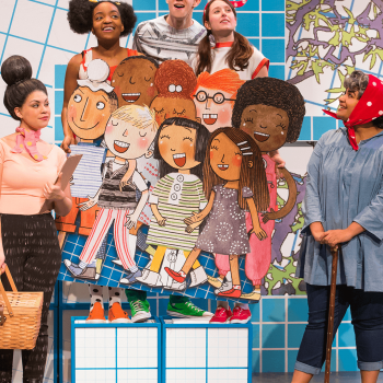Actors playing school children on stage with cardboard cutouts of children's book illustrations.