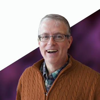Steve Carignan wearing a rust colored sweater with a purple and white background.