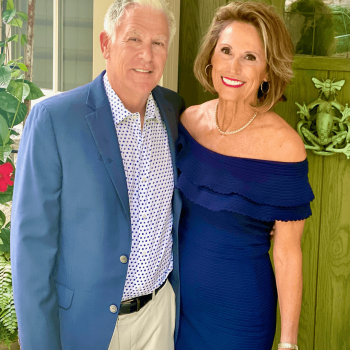 Terri and Steve in dress clothes standing and smiling in front of their home