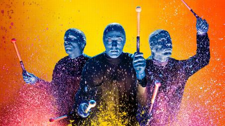 Blue Man Group on an orange and yellow background playing drums with paint