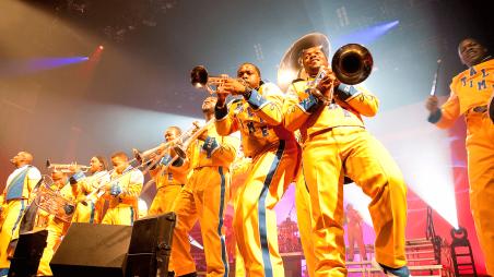 Men in orange jumpsuits playing brass instruments.