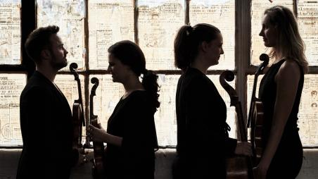 Members of the quartet in silhouettes holding their instruments