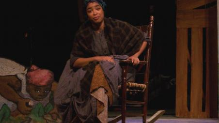 Actor sitting in a rocking chair on stage.