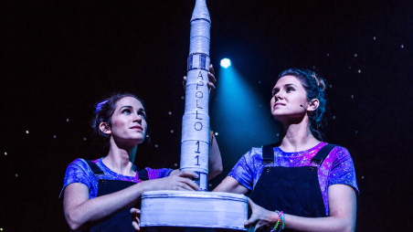 Two people hold up a model rocket of a spacecraft