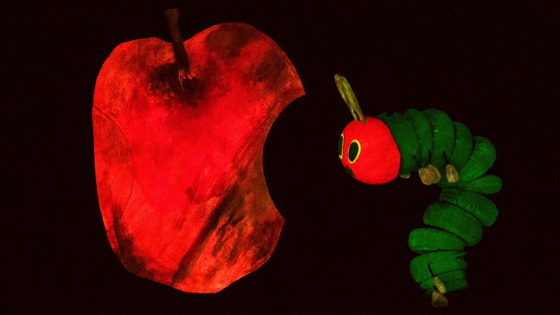 A puppet of a caterpillar and a red apple