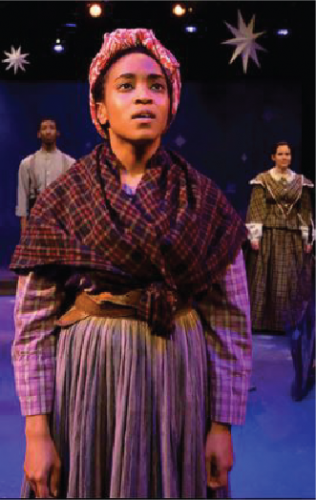 Actor portraying Harriet Tubman in a period costume looking upwards. There are other actors behind them and a starry background.